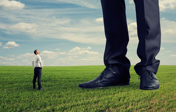 22087658 - small businessman looking at his big boss. photo on green field